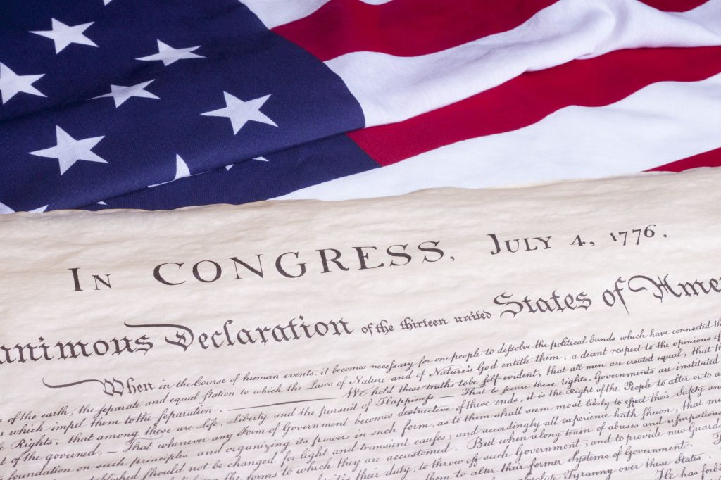 Declaration of Independence with American flag in background.